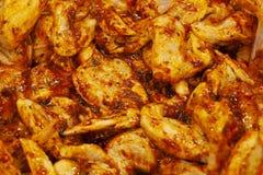 Rohe Hühnerflügel in der Marinade mit Pfeffer pökeln stockfoto