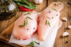 Rohe Hühnerleiste mit Knoblauch, Pfeffer, Olivenöl und Rosmarin Stockfotos