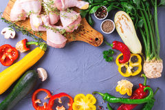 Rohe Hühnerschenkel mit verschiedenen Gemüsebestandteilen Beschneidungspfad eingeschlossen Stockbild