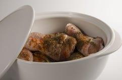 Rohe Hühnertrommelstöcke mariniert in den Gewürzen in einer großen weißen keramischen Kasserolle mit einem Deckel stockfotos