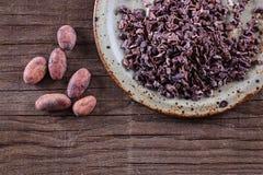 Rohe Kakao-Spitzen und Kakaobohnen über rustikalem hölzernem Hintergrund Stockfotografie
