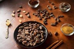 Rohe Kakaobohnen, Kakaopulver und brauner Zucker auf dunklem Steinhintergrund Stockfoto