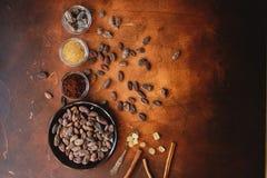 Rohe Kakaobohnen, Kakaopulver und brauner Zucker auf dunklem Steinhintergrund Lizenzfreie Stockfotos