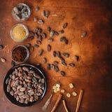 Rohe Kakaobohnen, Kakaopulver und brauner Zucker auf dunklem Steinhintergrund Stockbilder