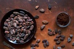 Rohe Kakaobohnen, Kakaopulver und brauner Zucker auf dunklem Steinhintergrund Stockfotografie