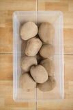 Rohe Kartoffeln in einem Plastikbehälter auf Boden Lizenzfreie Stockfotos