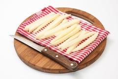Rohe Kartoffeln für Pommes-Frites und ein hölzernes Küchenmesser Stockfotos