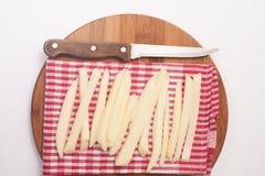 Rohe Kartoffeln für Pommes-Frites und ein hölzernes Küchenmesser Stockfotografie