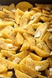 Rohe Kartoffeln mit den Gewürzen bereit gebraten zu werden Stockbilder