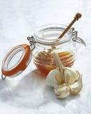 Rohe Knoblauchzehen und Honey Jar Lizenzfreie Stockbilder