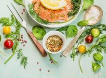 Rohe Lachse mit Frischgemüse und Kräutern, Vorbereitung für das Kochen auf grünem hölzernem Hintergrund Lizenzfreie Stockbilder