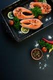 Rohe Lachssteaks auf einem dunklen Hintergrund Lizenzfreie Stockbilder