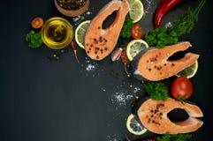 Rohe Lachssteaks auf einem dunklen Hintergrund Lizenzfreie Stockfotografie