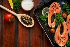 Rohe Lachssteaks auf einem hölzernen Hintergrund Stockfotografie