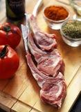 Rohe Lammhiebe mit Tomaten und herbals auf einem hölzernen Hintergrund Lizenzfreie Stockfotografie