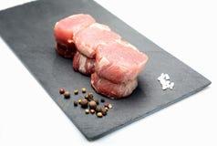 Rohe Leistenmedaillons des jungen Schweinefleisch mit Gewürzen auf dem Brett des schwarzen Basalts auf einem weißen Hintergrund Lizenzfreie Stockbilder
