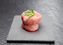 Rohe Leistenmedaillons des jungen Schweinefleisch mit Petersilie auf einem Brett des schwarzen Basalts auf einem grauen Hintergru Lizenzfreie Stockfotografie