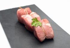 Rohe Leistenmedaillons des jungen Schweinefleisch mit Petersilie auf einem Brett des schwarzen Basalts auf einem weißen Hintergru Stockfoto