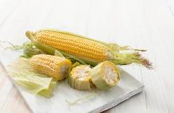 Rohe Maiskörner auf einer weißen Tabelle Stockbild