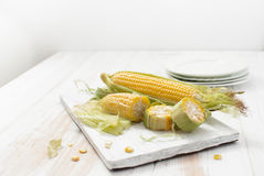 Rohe Maiskörner auf einer weißen Tabelle Stockbilder