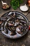 Rohe Miesmuscheln im Wasser auf dunklem Holztisch, Vorbereitung für das Kochen Lizenzfreie Stockfotografie