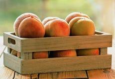 Rohe organische Pfirsiche in einer Holzkiste stockfotos