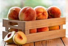 Rohe organische Pfirsiche in einer Holzkiste stockbilder
