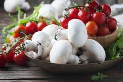 Rohe Pilze, Tomate und Rakete auf dem Holztisch lizenzfreie stockfotografie