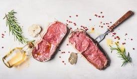 Rohe Rindfleisch Striploin-Steaks mit Öl, Gewürzen und Fleisch gabeln auf weißem Steinhintergrund, Draufsicht, flach Lage Stockfoto