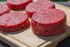 Rohe Rindfleischburger schließen oben auf einem hackenden Brett Lizenzfreies Stockbild