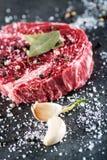 Rohe Rindfleischsteakleiste mit Bestandteilen mögen Seesalz, -pfeffer, -Lorbeerblätter und -zwiebel auf schwarzem Brett, Bild für Lizenzfreies Stockbild