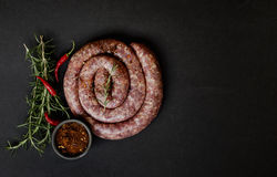 Rohe Rindfleischwürste auf einer Gusseisenwanne, selektiver Fokus Lizenzfreie Stockfotos