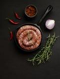 Rohe Rindfleischwürste auf einer Gusseisenwanne, selektiver Fokus lizenzfreie stockbilder