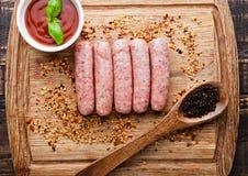 Rohe Rindfleischwürste mit Pfeffer Löffel und sause an Bord Lizenzfreies Stockbild