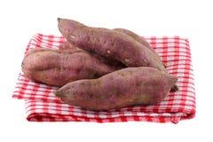 Rohe Süßkartoffel mit Schmutz auf Haut Stockfotografie