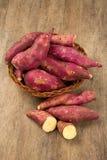 Rohe Süßkartoffeln auf hölzerner Hintergrundnahaufnahme Lizenzfreie Stockfotos