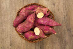 Rohe Süßkartoffeln auf hölzerner Hintergrundnahaufnahme Stockfotografie