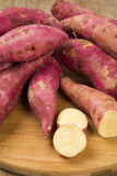 Rohe Süßkartoffeln auf hölzerner Hintergrundnahaufnahme Stockbild