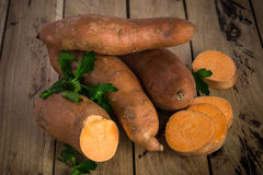 Rohe Süßkartoffeln auf rustikalem hölzernem Hintergrund Lizenzfreie Stockfotos