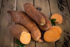 Rohe Süßkartoffeln auf rustikalem hölzernem Hintergrund Stockbild