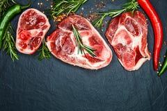 Rohe saftige Fleischsteaks bereit zur Röstung und zu den vegatables auf einem bla Lizenzfreies Stockfoto
