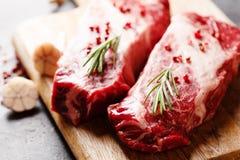 Rohe schwarze Angus Prime-Fleischsteaks auf hölzernem Brett lizenzfreie stockfotografie