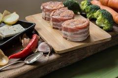 Rohe Schweinefiletmedaillons gefüllt mit Chorizo und mit Speck eingewickelt Lizenzfreies Stockfoto