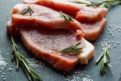 Rohe Schweinefleischsteaks mit Rosmarin stockfotografie