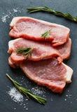 Rohe Schweinefleischsteaks mit Rosmarin lizenzfreie stockfotos
