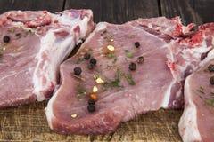 Rohe Schweinekoteletts mit Gewürzen auf einem hölzernen Brett stockbilder