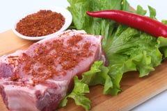 Rohe Schweinekoteletts mit Kräutern und Gewürzen auf Schneidebrett Bereiten Sie für das Kochen vor Stockfotografie