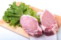 Rohe Schweinekoteletts mit Kräutern und Gewürzen auf Schneidebrett Bereiten Sie für das Kochen vor Lizenzfreie Stockbilder
