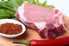 Rohe Schweinekoteletts mit Kräutern und Gewürzen auf Schneidebrett Bereiten Sie für das Kochen vor Lizenzfreie Stockfotografie