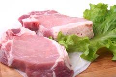 Rohe Schweinekoteletts mit Kräutern und Gewürzen auf Schneidebrett Bereiten Sie für das Kochen vor Stockfoto
